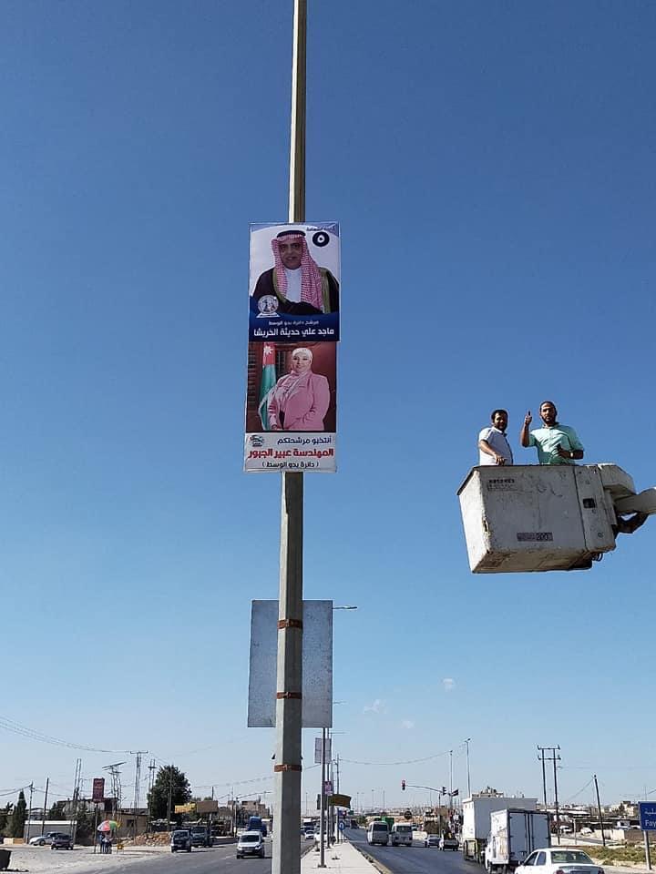 مؤيدون للمرشح ماجد الخريشا يقومون بتعليق صورة متطايرة للمرشحة عبير الجبور